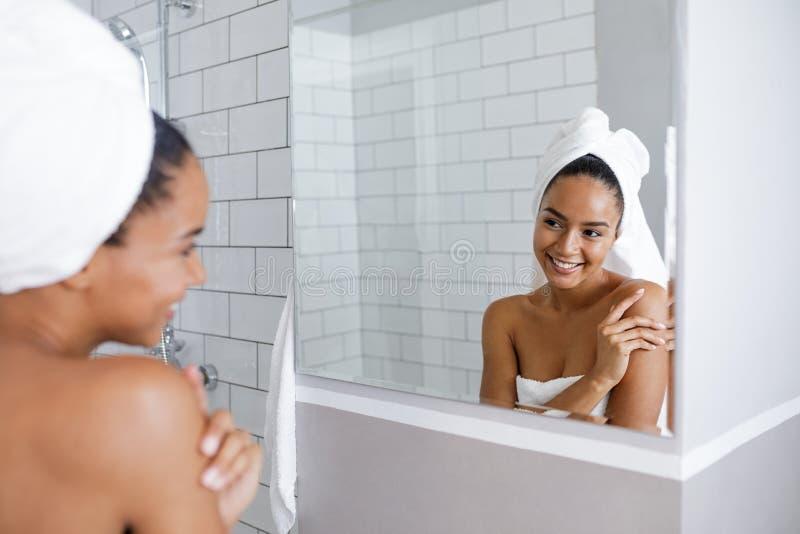 Schöne Mischrassefrau, die ihre Reflexion im Spiegel betrachtet stockbild