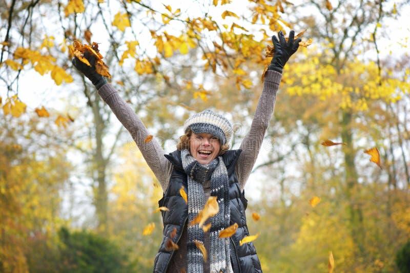 Schöne Mitte gealterte Frauen-werfende Gelb-Blätter stockfoto
