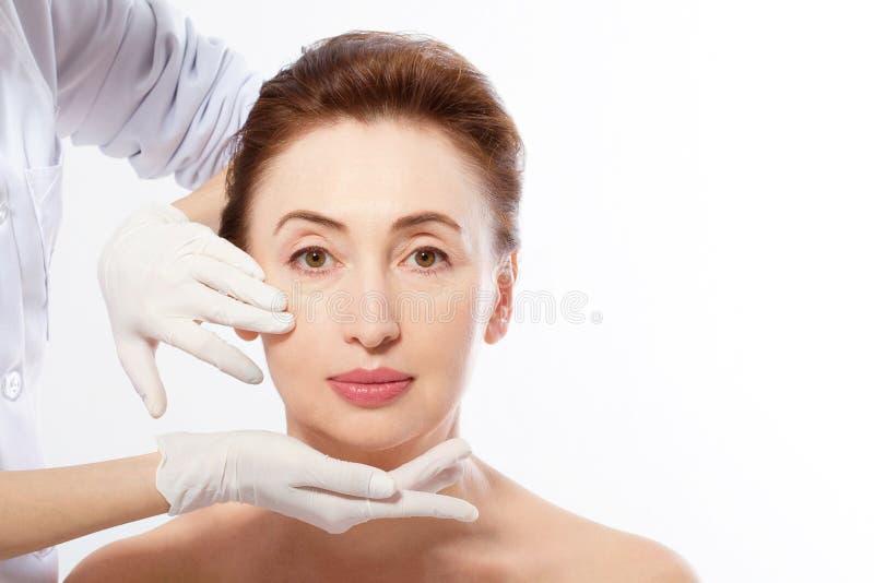 Schöne Mittelalter-Frau vor plastischer Chirurgie Makrogesicht mit Falten und Doktor ` s Händen lokalisiert auf weißem Hintergrun lizenzfreie stockfotos