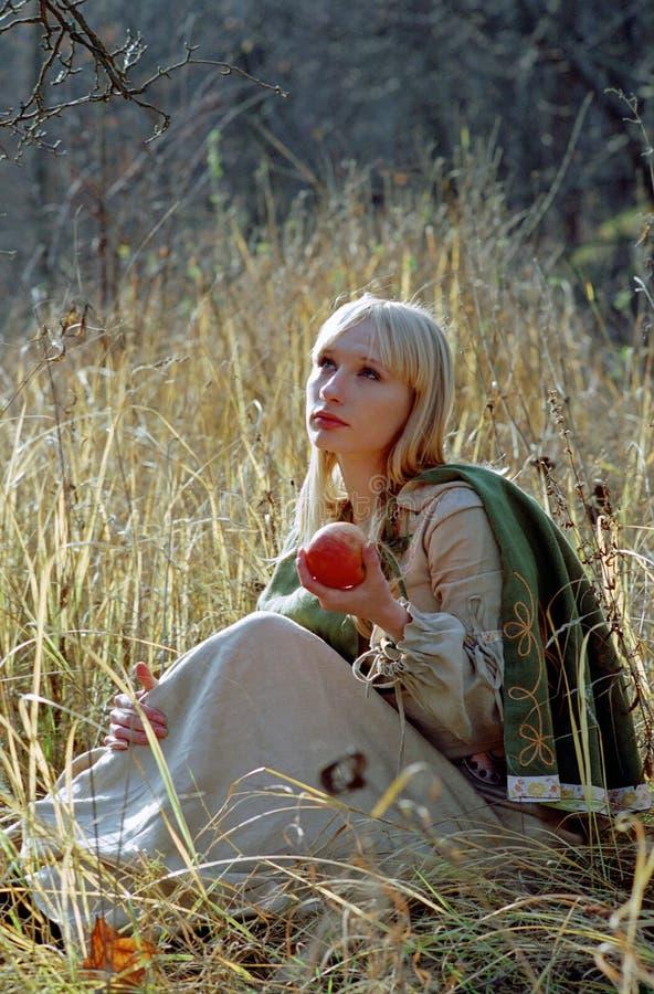 Schöne mittelalterliche Frau, die auf Lichtung sitzt lizenzfreie stockbilder