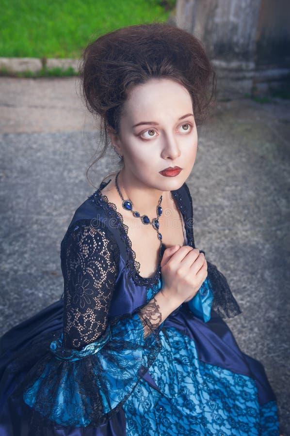 Schöne mittelalterliche Frau im blauen Kleid betend stockbild
