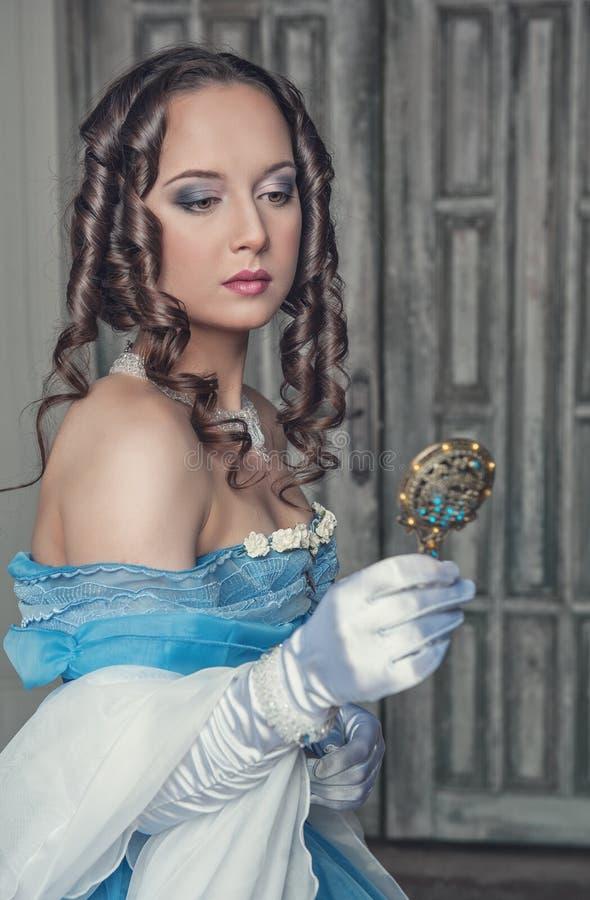 Schöne mittelalterliche Frau im blauen Kleid mit Spiegel lizenzfreie stockfotografie