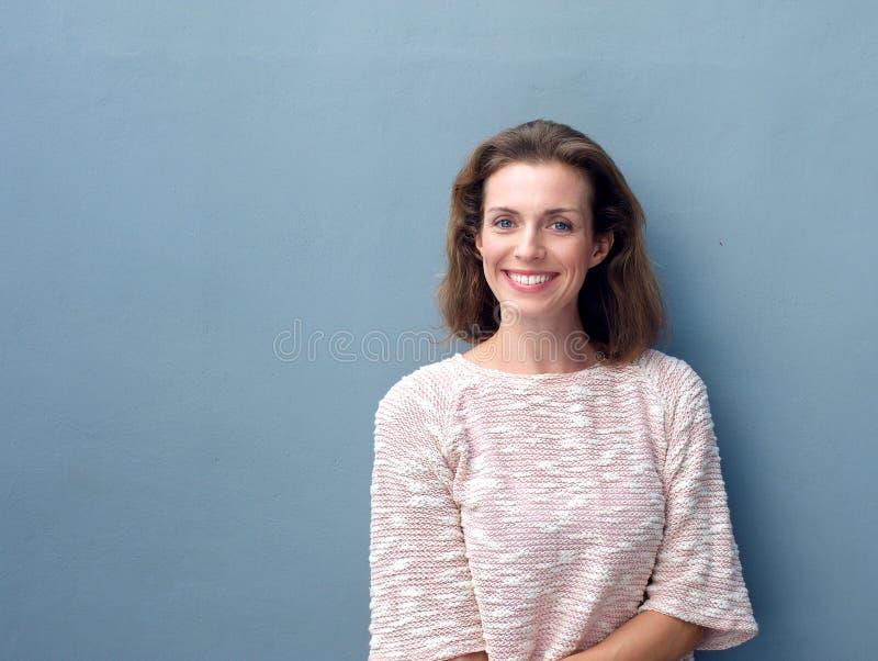 Schöne mittlere erwachsene Frau, die auf grauem Hintergrund lächelt stockbild
