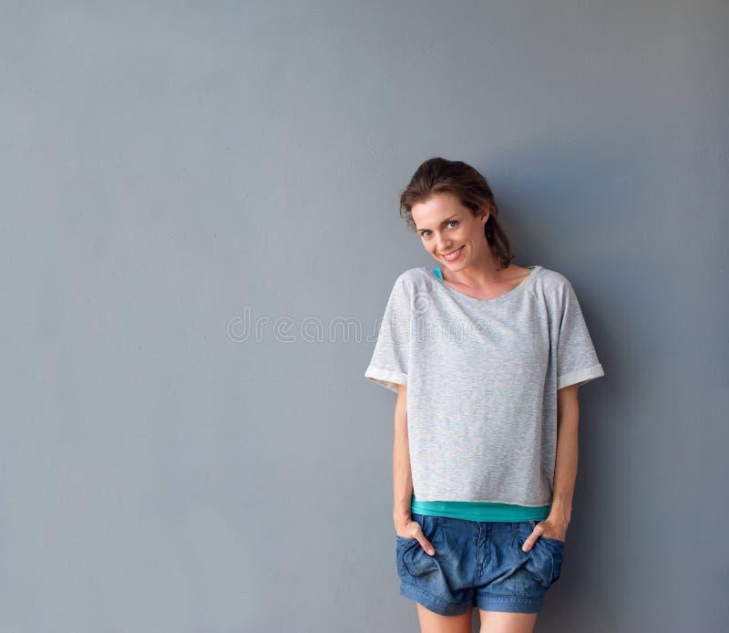 Schöne mittlere erwachsene Frau, die gegen grauen Hintergrund lächelt lizenzfreie stockfotografie