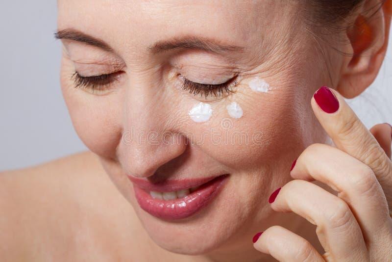 Schöne mittlere Greisin, die kosmetische Sahnebehandlung auf Gesicht auf grauem Hintergrund anwendet Spott hoch und Kopienraum ge lizenzfreies stockfoto