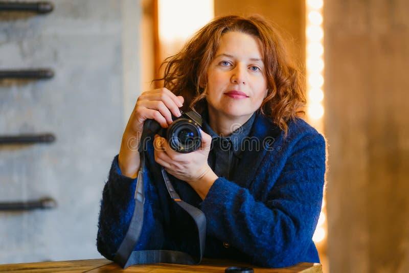 Schöne mittlere Greisin mit einer Kamera in ihren Händen, welche die Kamera betrachten stockfoto