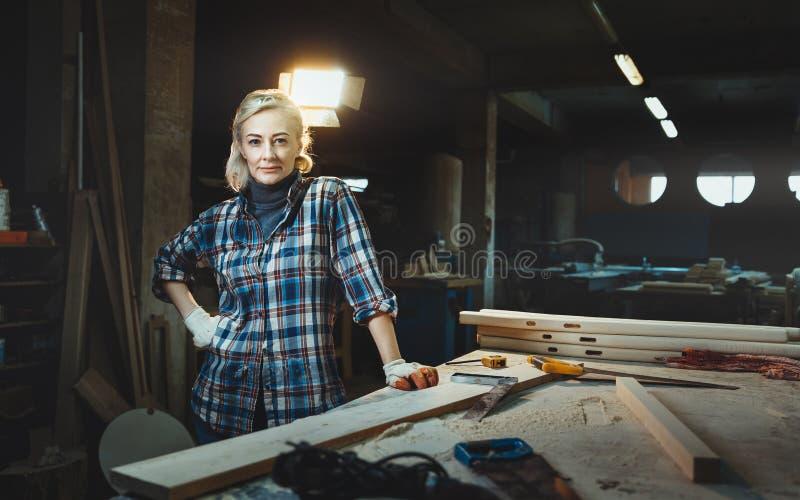 Schöne mittlere Greisinarbeitskraft, die gegen Hintergrund einer Holzbearbeitungswerkstatt aufwirft Konzept von motivierten Fraue lizenzfreie stockfotografie