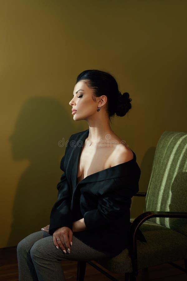 Schöne Mode Nude selbstbewusste Frau mit schwarzem Haar sitzend auf einem Stuhl in einer schwarzen Jacke Perfekte Körperglatte, s stockbilder