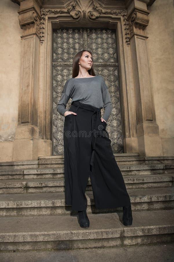 Schöne Modedame, die nahe der alten Weinlesetür trägt grauen Mantel aufwirft stockbilder