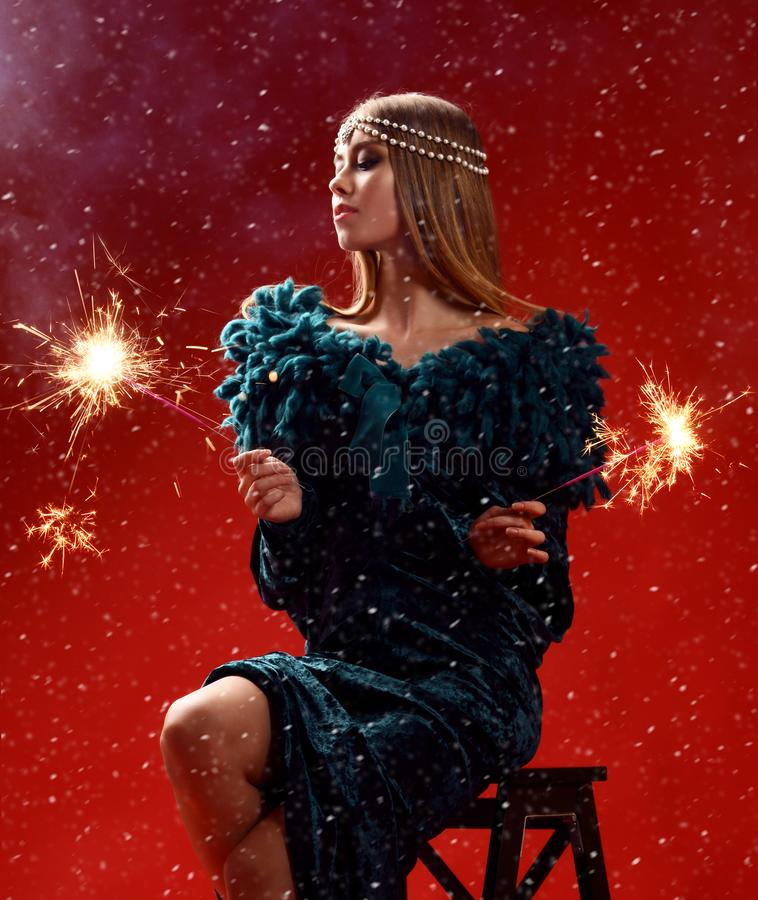 Schöne Modefrau, die zwei Wunderkerzen im dunkelgrünen Kleid auf rotem Weihnachten hält stockbilder