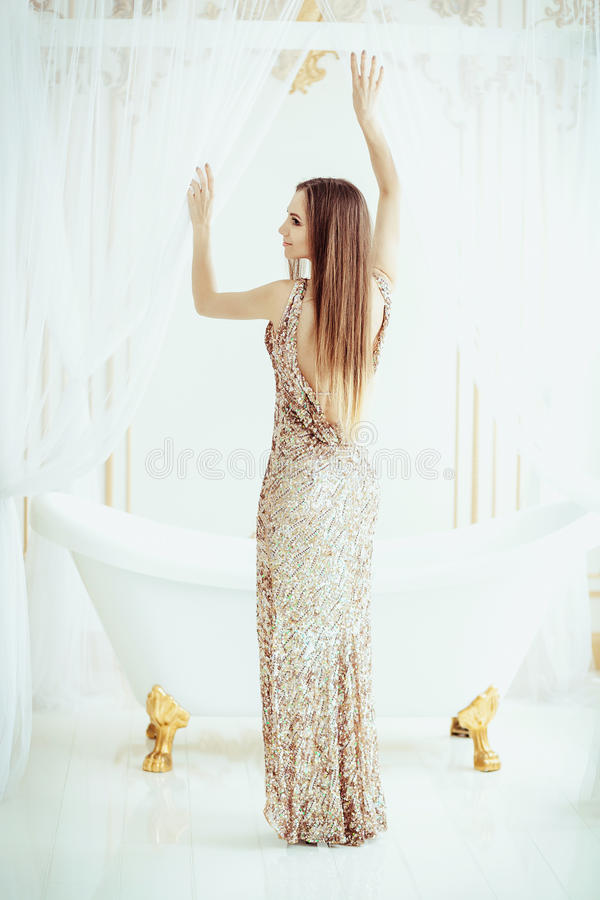 Schöne Modefrau im Goldkleid, elegante Dame, die nahe weißem Bad steht Purpurrotes Make-up und bunte helle Nägel frisur Brunettem lizenzfreies stockfoto