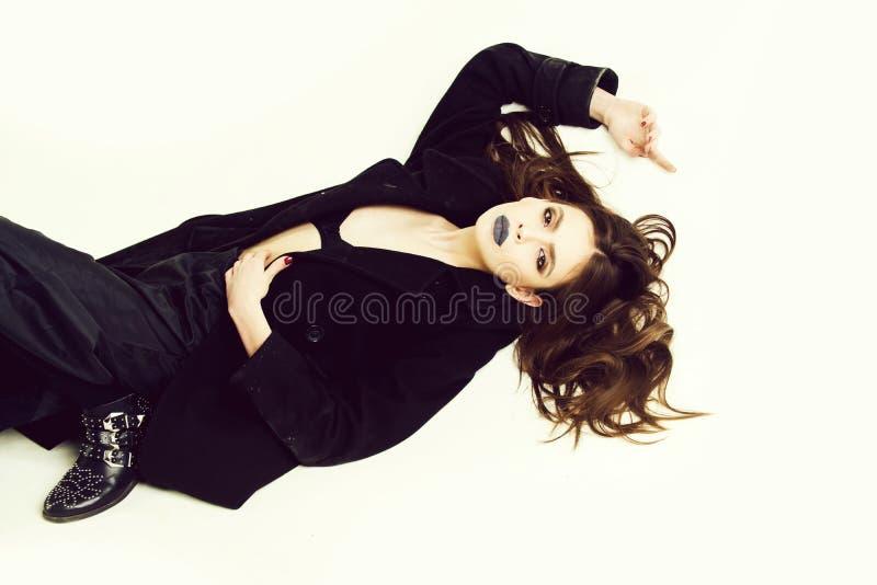 schöne Modefrau im schwarzen Mantel lokalisiert auf weißem Hintergrund stockfotografie