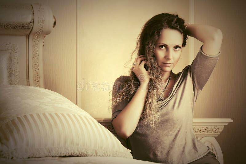 Schöne Modefrau mit den langen gelockten Haaren in einem Schlafzimmer stockfotos