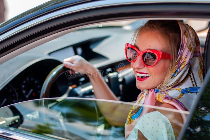 Schöne Modefrau mit den roten Lippen und Sonnenbrille im Auto stockfoto