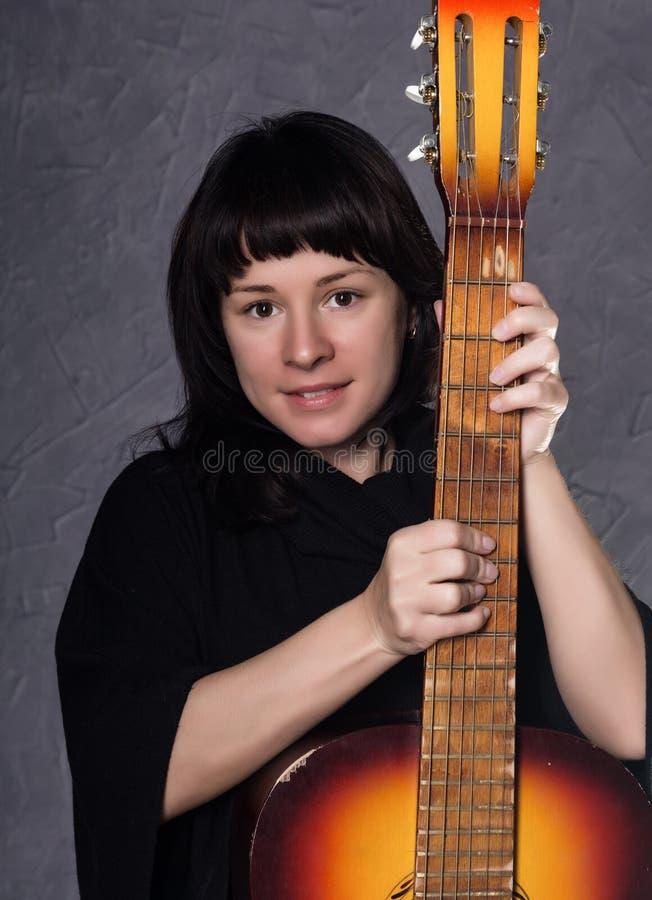 Schöne moderne Dame, die ein gotisches schwarzes Kleid mit hohem Kragen, Haltungen mit einer Akustikgitarre auf einem Grau trägt stockbild