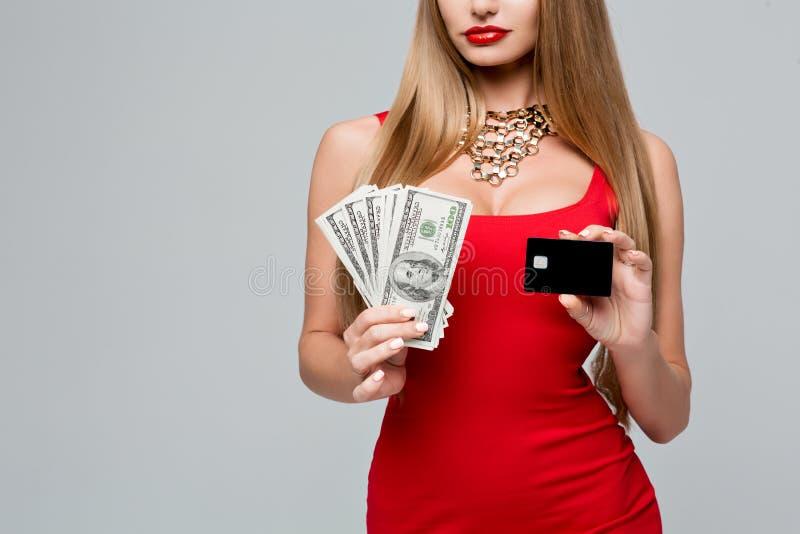 Schöne moderne Frau hält das Geld und die Kreditkarte Stilvolle schlanke Frau in einem roten Kleid mit den roten Lippen stockbild