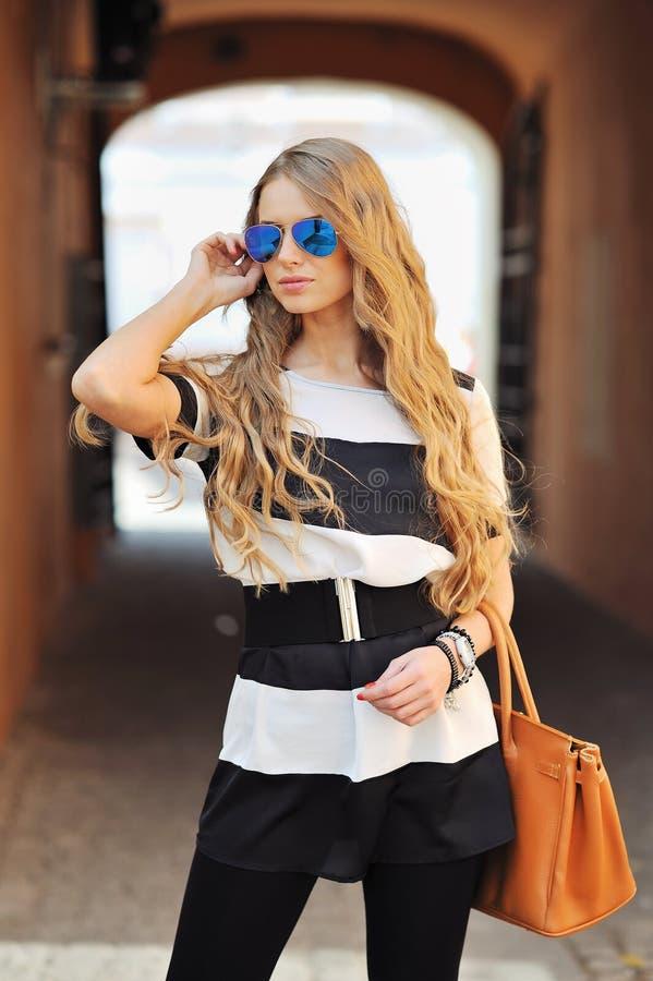 Schöne moderne Frau mit dem langen blonden Haar, schoss draußen stockfoto