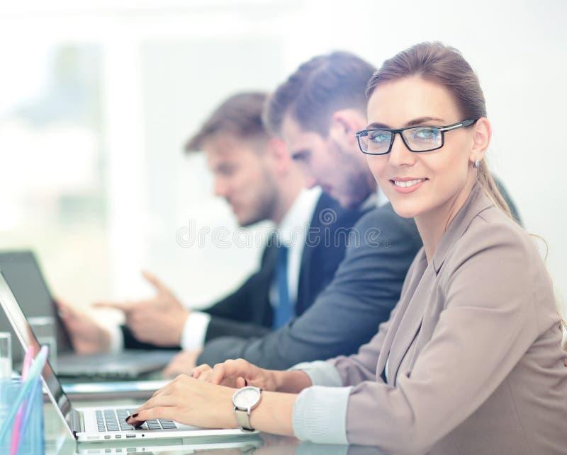 Schöne moderne Geschäftsfrau, die an mit ihren Kollegen arbeitet stockfotos