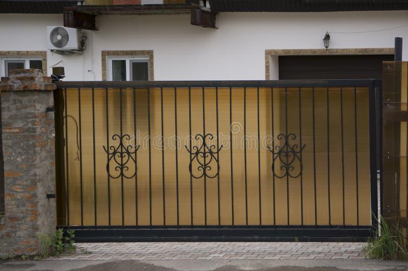 Schöne, moderne Schmiedeeisentore, Eingang zum Hof lizenzfreie stockfotos