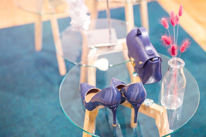 Schöne moderne stilvolle ultraviolette Farbfrauenschuhe und -Zubehör auf einem Glastisch Polierleder bigtime des jungen Mädchens stockbilder