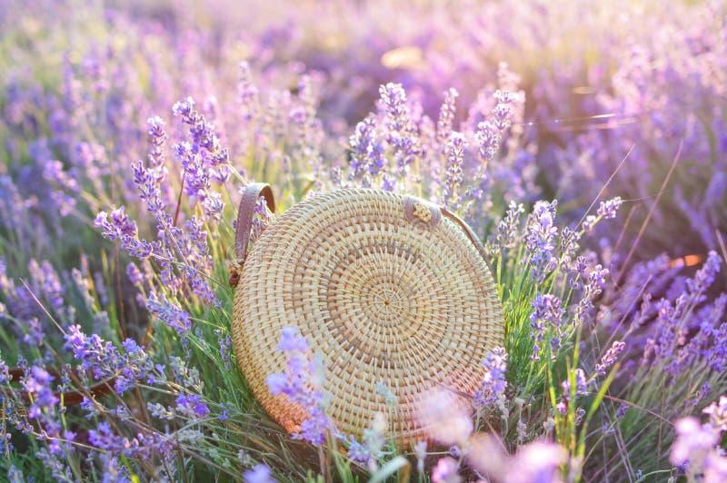 Schöne modische Frauenstroh-Kreistasche auf einem Lavendelgebiet Das Konzept von Sommer restNature Art und Weise lizenzfreie stockfotos