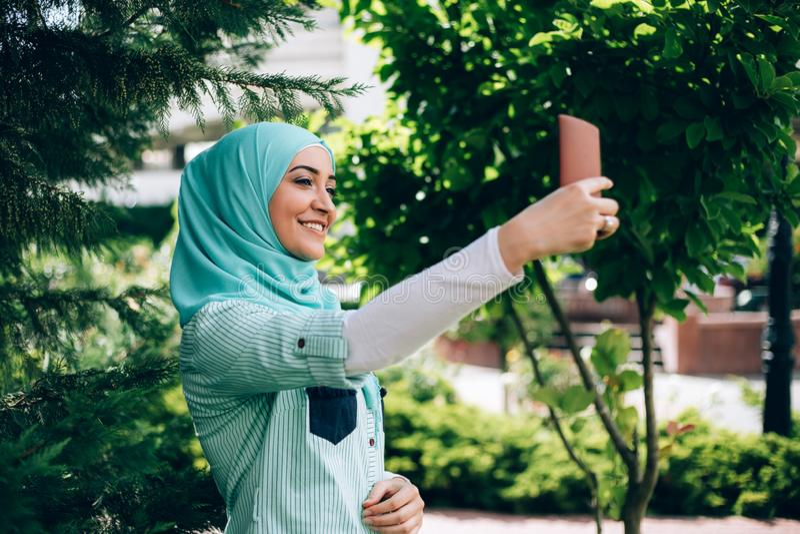 Schöne moslemische Frau, die selfie durch Smartphone an der Straße macht stockbild