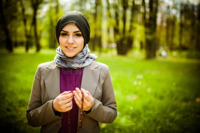 Schöne moslemische Frau tragendes hijab, das auf Rosenbeet/tespih betet lizenzfreies stockbild
