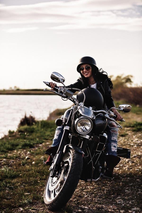 Schöne Motorrad Brunettefrau mit einem klassischen Motorrad c lizenzfreie stockfotos