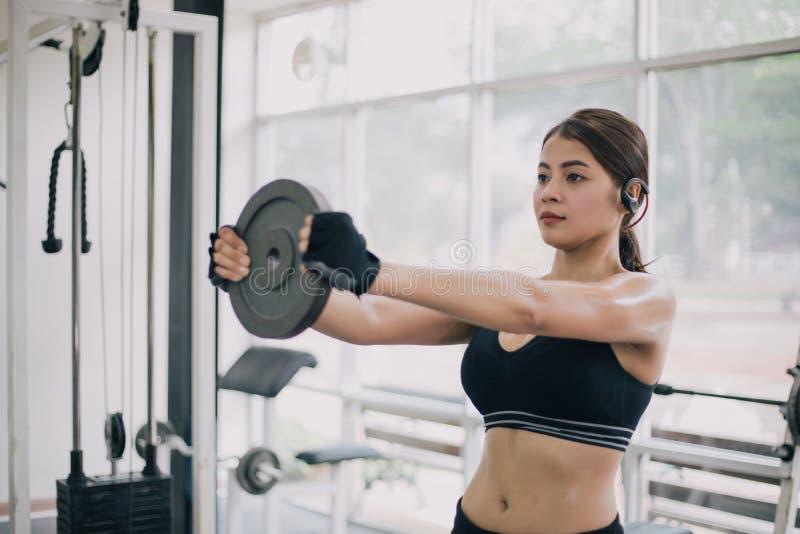 Schöne muskulöse Sitzfrau, welche die Gebäudemuskeln und Eignungsfrau tun Übungen in der Turnhalle ausübt Eignung - Konzept von stockfotos