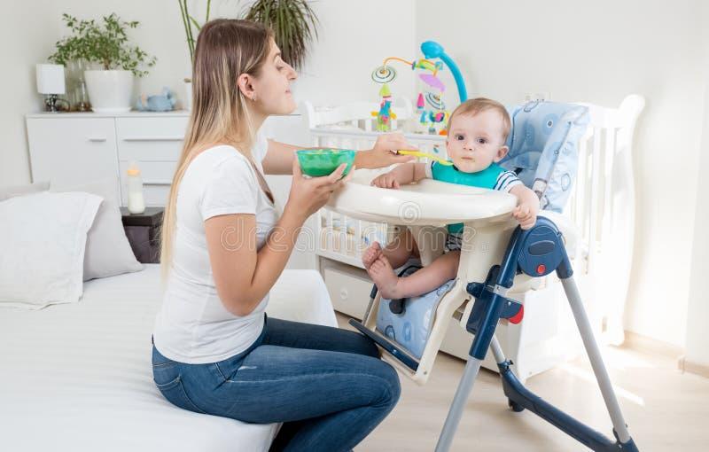 Schöne Mutter, die ihr Baby mit Fruchtsoße in hohem c einzieht lizenzfreies stockfoto