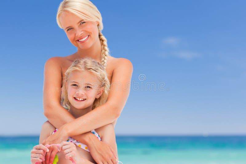 Schöne Mutter, die ihre Tochter umfaßt lizenzfreie stockfotos