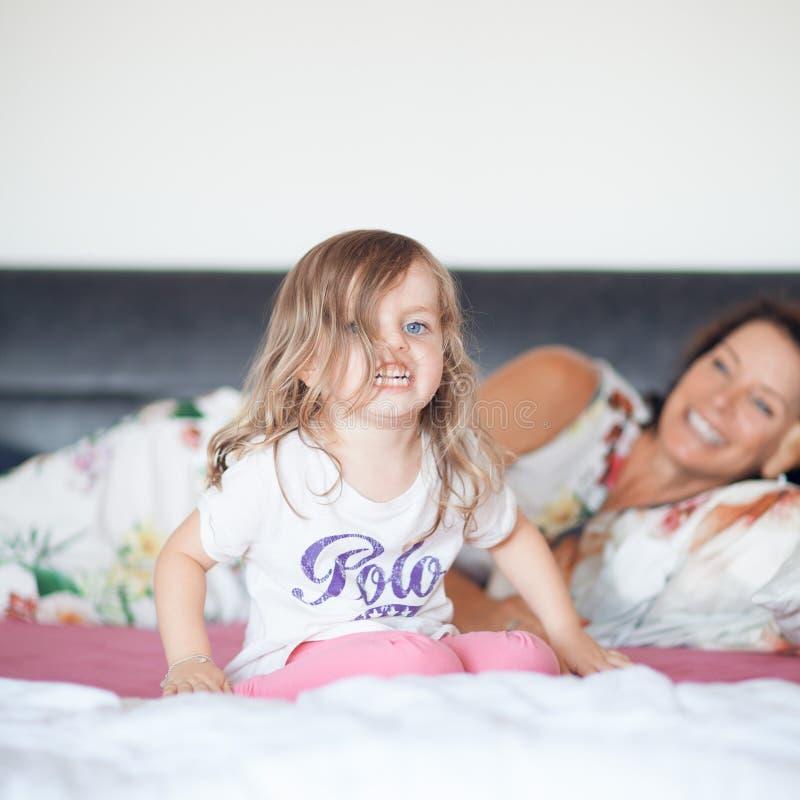 Schöne Mutter, die im Bett mit ihrer kleinen Tochter, Spaß habend liegt lizenzfreie stockfotos