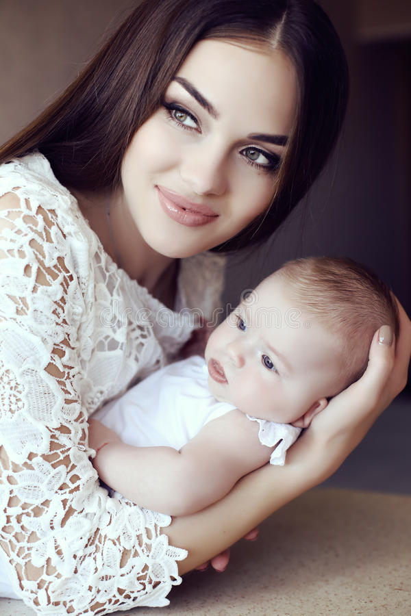 Schöne Mutter mit dem luxuriösen dunklen Haar und ihr kleines Baby lizenzfreie stockfotografie