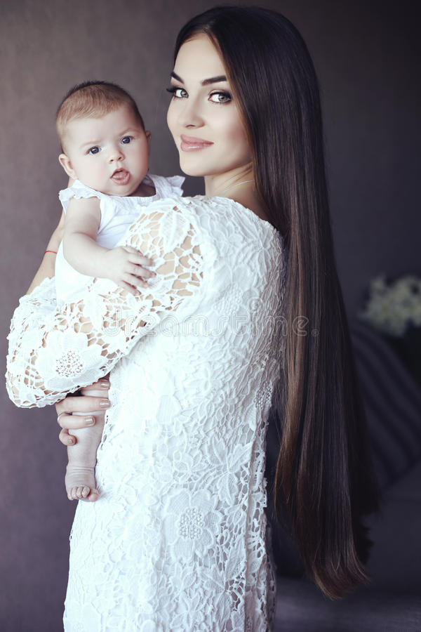 Schöne Mutter mit dem luxuriösen dunklen Haar und ihr kleines Baby stockfoto