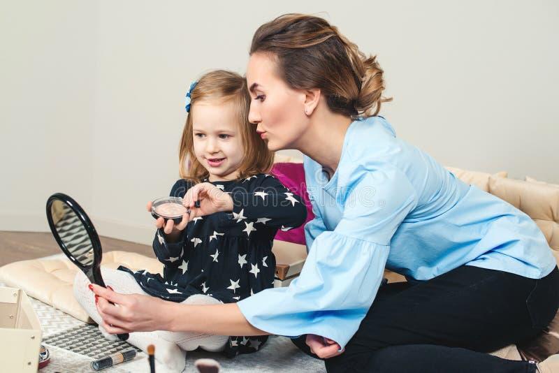 Schöne Mutter mit ihrer kleinen Tochter, die zuhause Make-up macht Junge Mutter und süße Kinder haben zu Hause Spaß stockbild