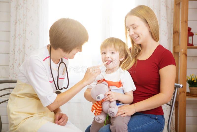 Schöne Mutter und ihr kleiner Sohn an der Aufnahme an Doktor lizenzfreie stockbilder