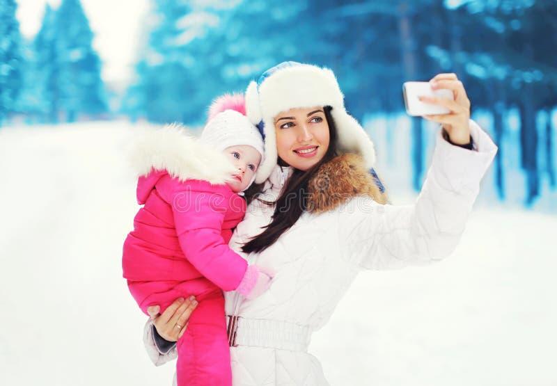 Schöne Mutter und Kind macht Fotoselbstporträt auf dem Smartphone im Winter stockbilder