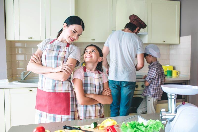 Schöne Mutter und Mädchen stehen zurück zu hinterem und betrachten einander Sie lächeln Mädchen haben ein Rest Jungen sind stockfotos