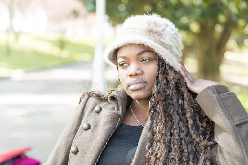 Schöne nachdenkliche afrikanische junge Frau mit Hut im Park lizenzfreies stockfoto
