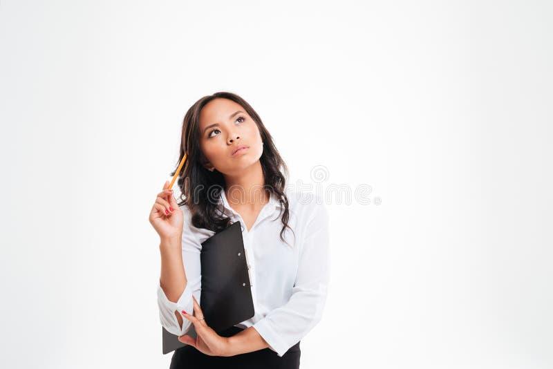Schöne nachdenkliche asiatische Geschäftsfrau, die Klemmbrett hält und an etwas denkt stockbilder