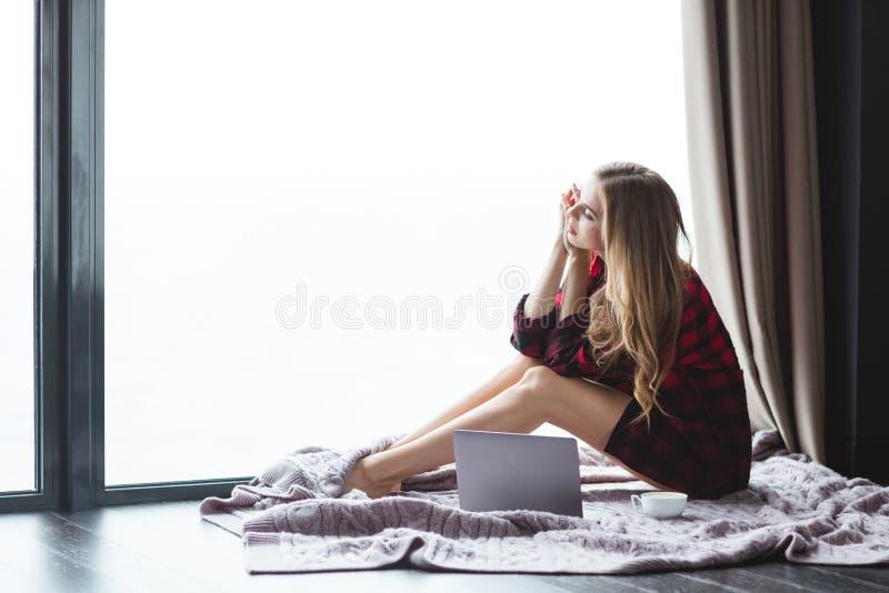 Schöne nachdenkliche Frau, die mit Laptop und Tasse Kaffee sitzt stockfoto
