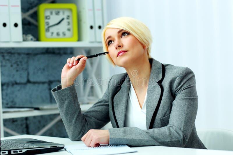 Schöne nachdenkliche Geschäftsfrau, die am Tisch sitzt stockbilder