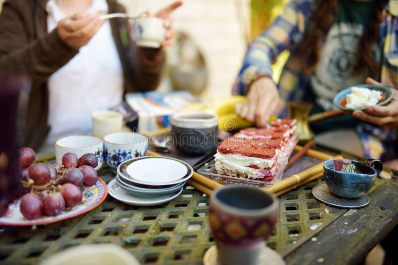 Schöne Nachtischtabelle mit bunten keramischen Schalen, Untertassen, köstlichem Karottenkuchen und Früchten Essen von Bonbons und lizenzfreie stockfotografie