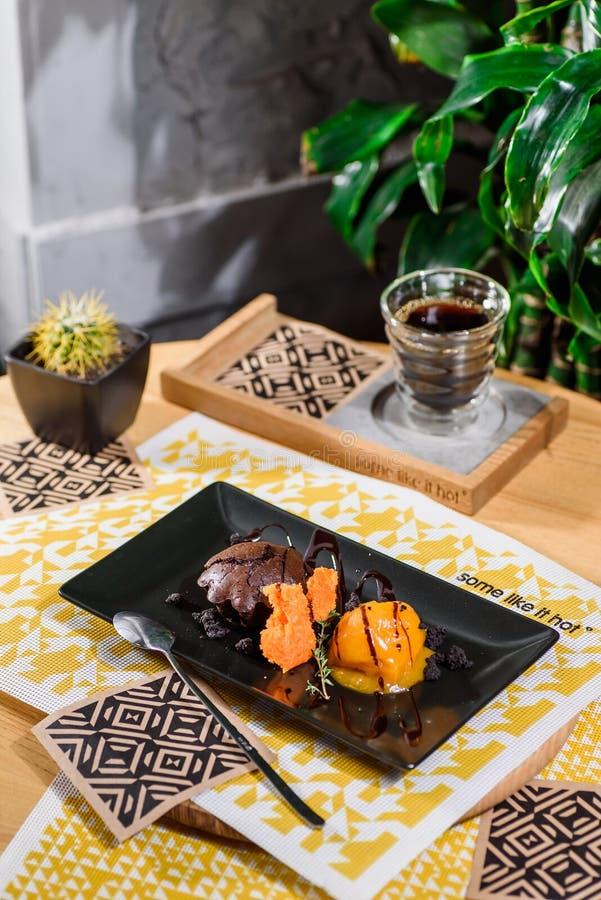 Schöne Nachtischumhüllung - Schokoladenkuchen und MangoEiscreme mit Beerensirup auf einem Schwarzblech lizenzfreie stockfotos