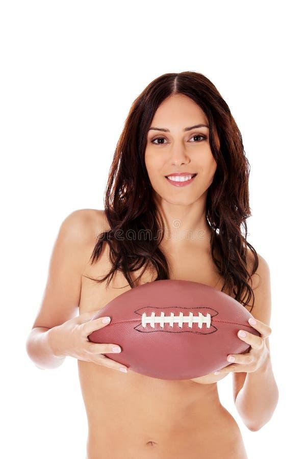 Schöne nackte Frau, die Ball des amerikanischen Fußballs hält stockfotografie