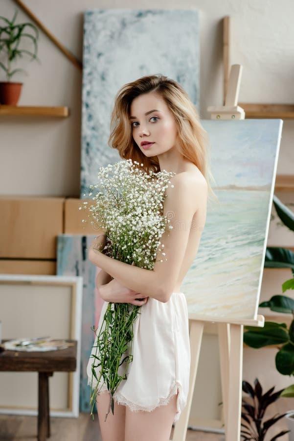 schöne nackte junge Frau, die weiße Blumen hält und Kamera im Kunststudio betrachtet stockfoto