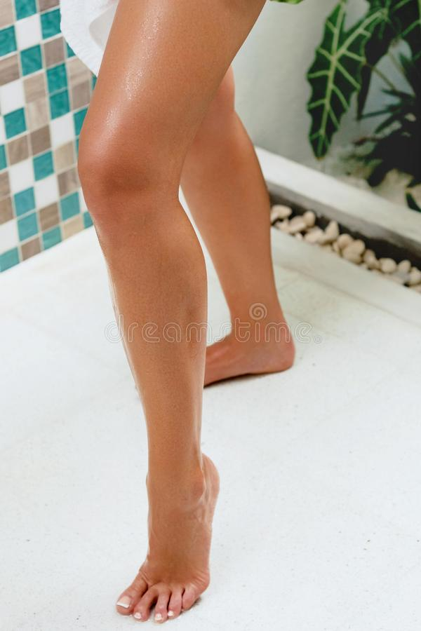 Schöne nass Füße, Frauenbeine und Hand Nahaufnahmefoto der netten hübschen jungen Frau, die ihre Beine berührt lizenzfreies stockbild