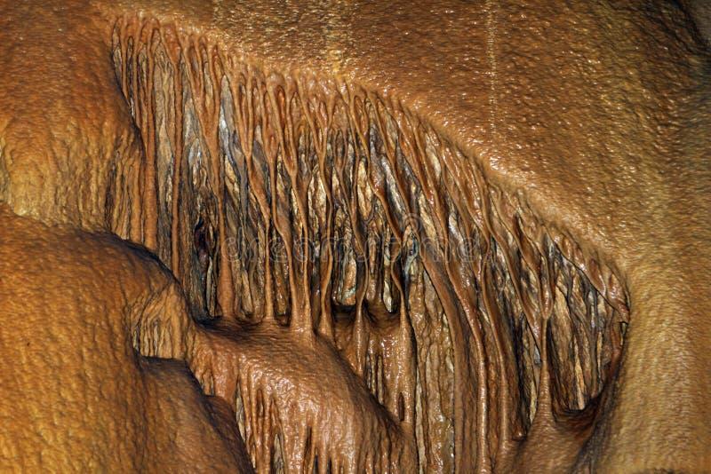 Schöne natürliche Höhle mit gingery Wänden und Bildungen von Stalagmiten überall, natürliches Beschaffenheitsfoto lizenzfreies stockfoto