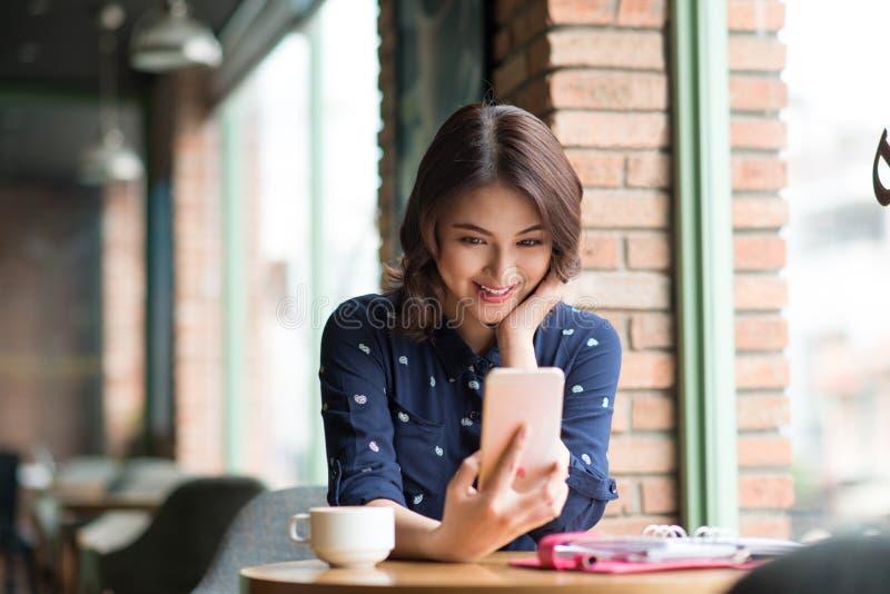 Schöne nette asiatische junge Geschäftsfrau im Café, sel nehmend stockbilder