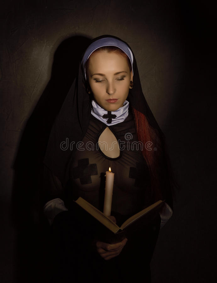 Schöne Nonne mit einer Kerze die Bibel lesend Religiöses Konzept lizenzfreie stockfotografie